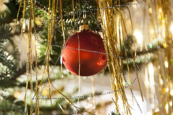 Eine rote Weihnachtskugel zwischen goldenem Lametta