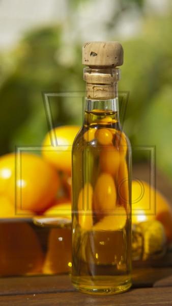 Olivenölfläschchen mit Zitrusfrüchten im Hintergrund
