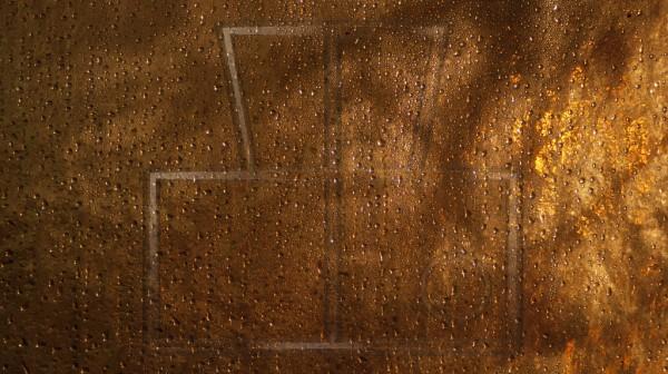 Wassertropfen auf Glas bei goldgelben Licht