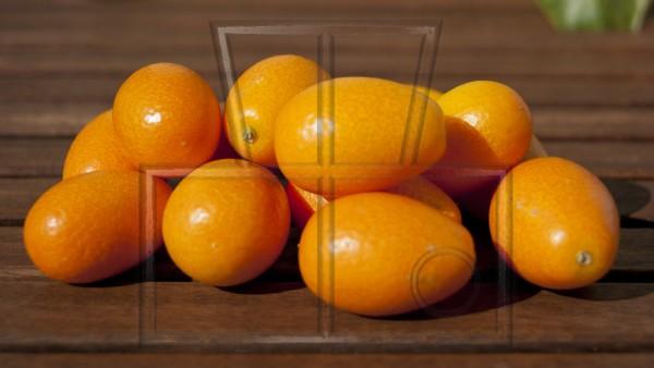 einige Kumquats auf einem dunklem Holzuntergund