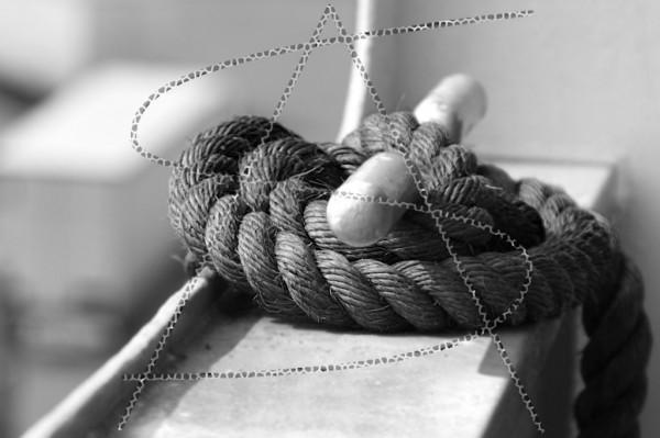 Schiffstau an der Reling befestigt als schwarz-weiß Bild