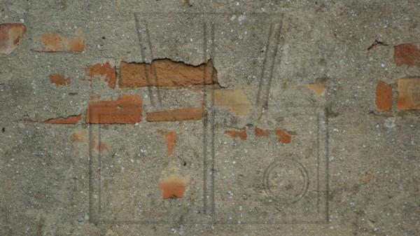 zum Teil noch verputzte, bröckelnde, alte, gelbrote Backsteinwand