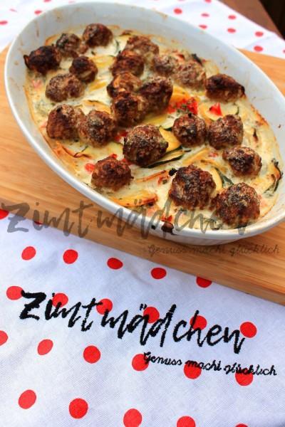 Auflaufform mit Zucchini-Kartoffel-Auflauf und Hackbällchen