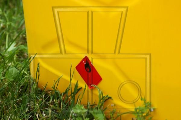 gelber Kanister mit Flüssigkeit der Gefahrklasse A III auf Rasen