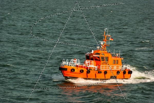 Backbordseite eines leuchtend orangenen Lotsenboots