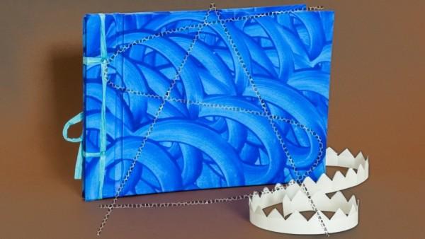 blaues Fotobuch mit Fotoecken und stilisiertem Hintergrund