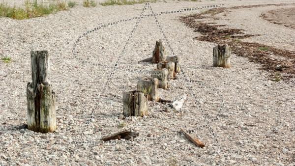 Reste alter Holzpfähle im Steinstrand